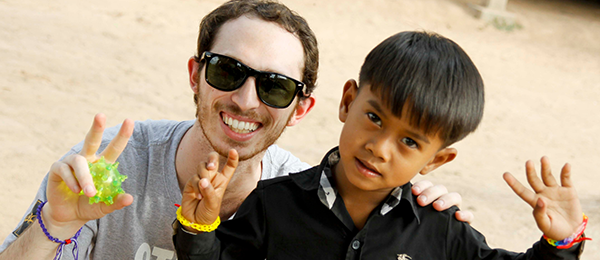 A student poses for a picture with a little boy