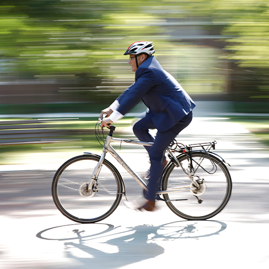 President Crawford wearing a helmet and business suit rides his bike. The passing scenery is blurred.