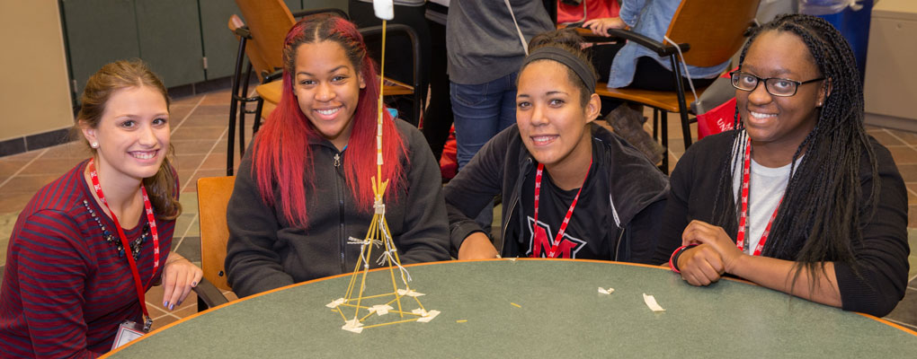 Four female students pose with a structure made out of dry spaghetti noodles and string