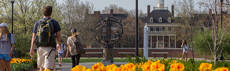Students walking on campus with the Sundial and MacCracken Hall in the background