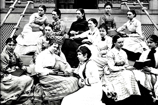 The women of the Western College Class of 1877 sit together on the steps of Peabody Hall