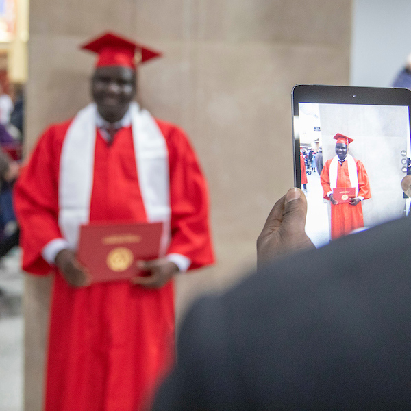 A black parent takes a photo of his graduating student with his phone.