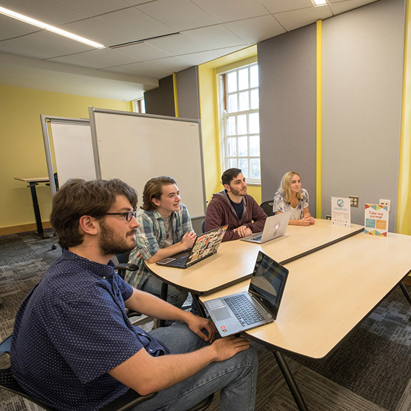 Four student consultants gather at a table in the Howe Center for Writing Excellence. They watch another consultant write on a whiteboard.