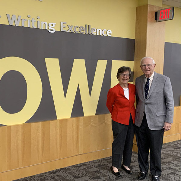 "HCWE founders Roger and Joyce Howe stand before sign that says ""HOWE."""