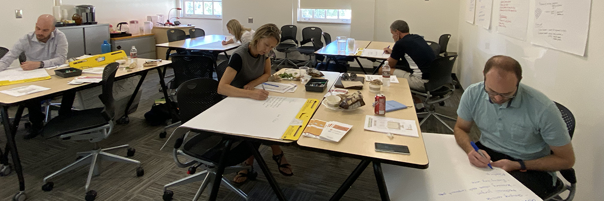 Professors sit 1 and 2 to a table writing on large Post-It notepads in the Howe Center for Writing Excellence.