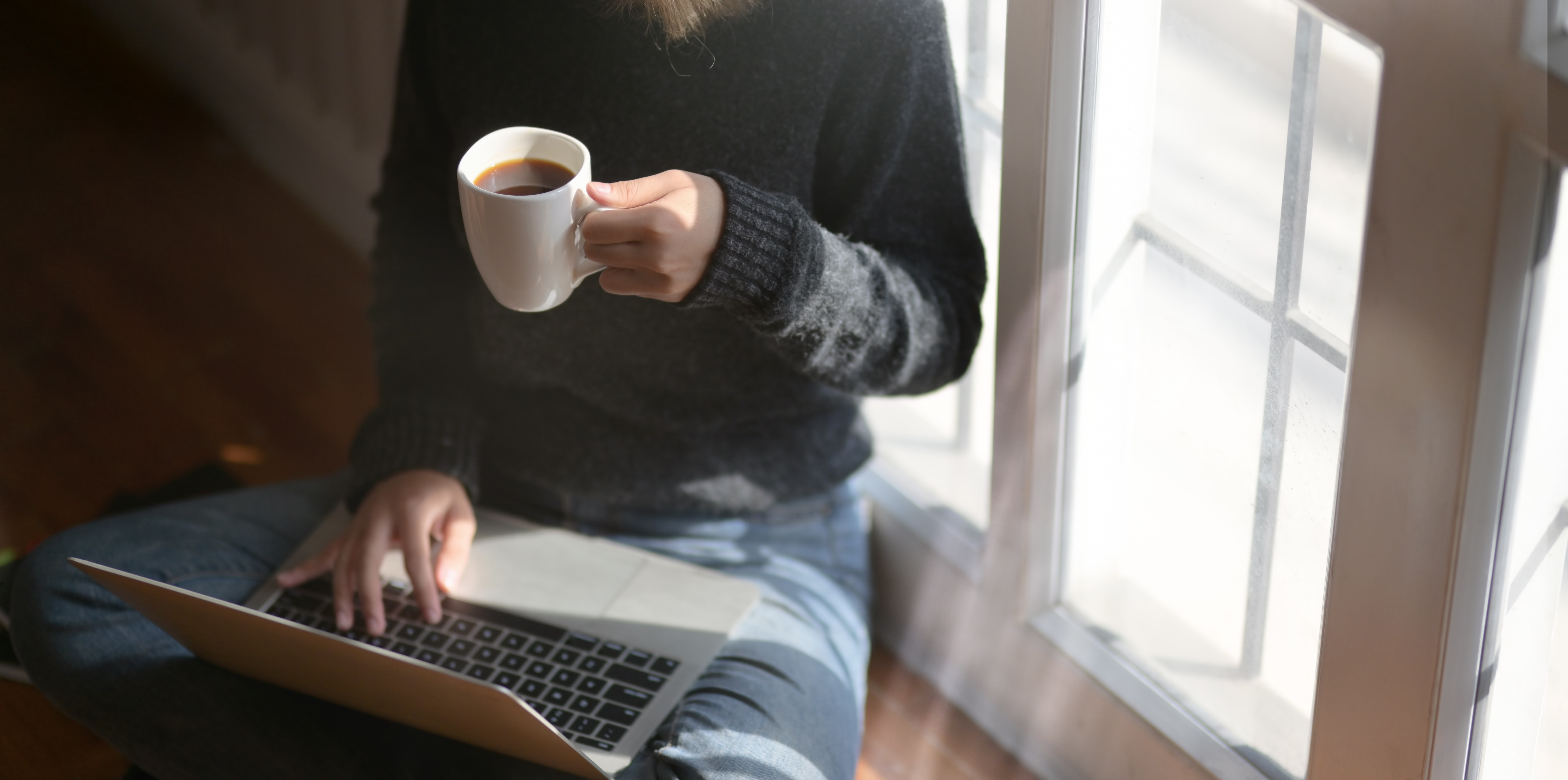 a person sitting on the floor with a laptop and a cup of coffee