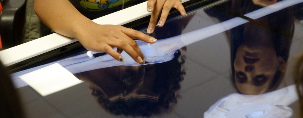 A student touches a table showing a virtual cadaver