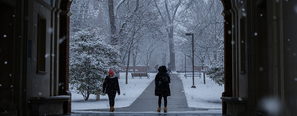 Bundled people walk under an archway in a snowstorm