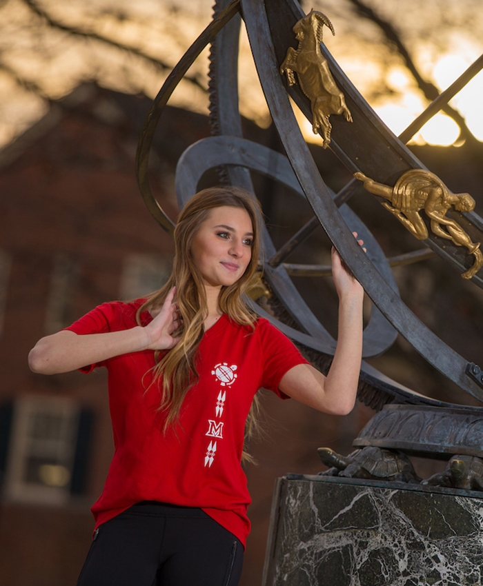 Student stands next to the sundial on central quad. She wears a red t-shirt with a design that includes the myaamia heritage logo, Miami University logo, and the Myaamia Heritage Turtle mark in a vertical pattern