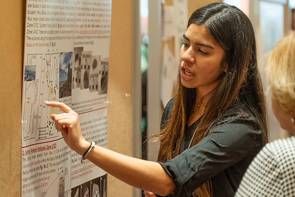 A graduate student points to a portion of her research poster as a visitor looks on