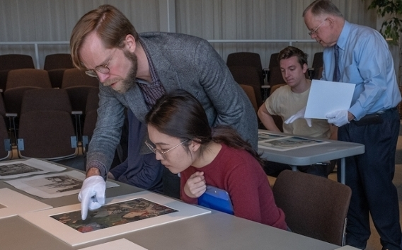 Michael Hatch, assistant professor of art history, discusses a print piece with a student, while Robert Wicks, director of the Miami University Art Museum, talks to another student in the class at the art museum.