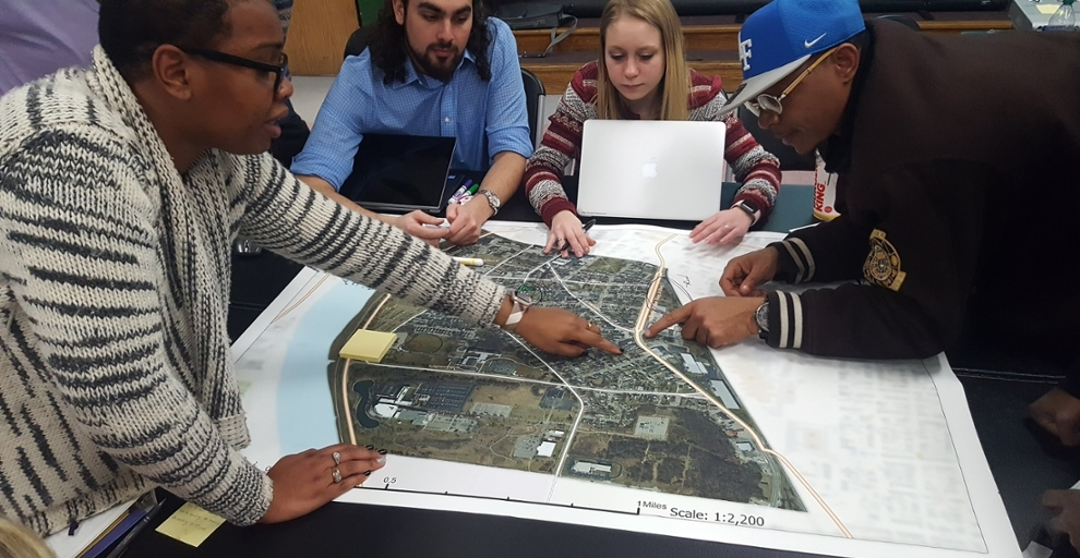 Miami students and Hamilton residents talk around a neighborhood map.
