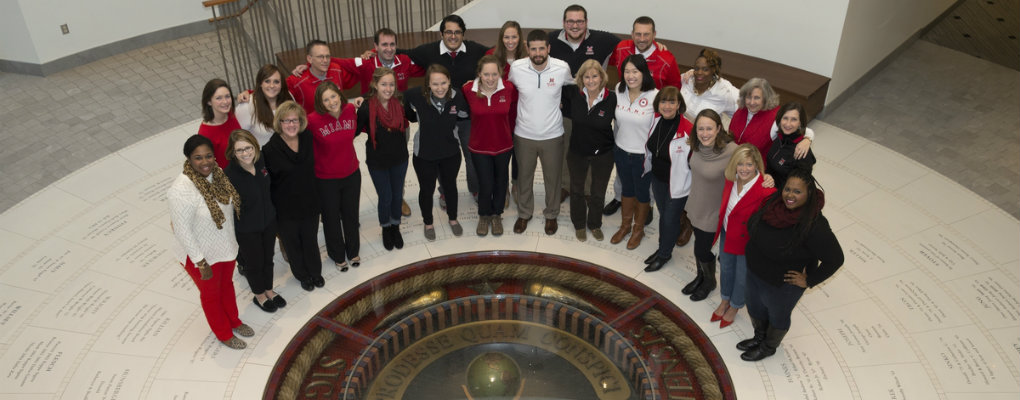 A group of admissions staff stand in a semicircle around the Miami seal in the floor of Armstrong Student Center