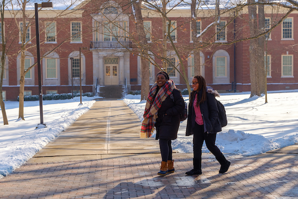 Two students walking to class while the campus is blanketed in snow.