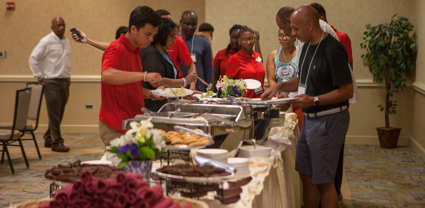 Shown is a photo of people making plates of food from catered food.