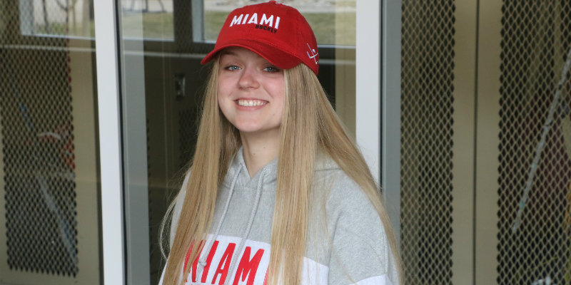 Woman wearing Miami Hockey hat and Miami Skating hoodie