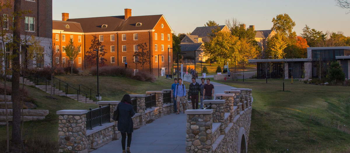 Students walking across a stone bridge on Western Campus.