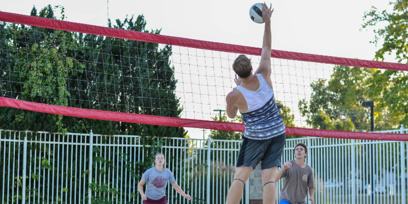 a male jumping in the air to spike a volleyball on the sand