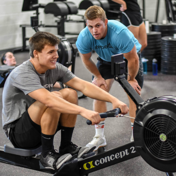 A student using a rowing machine