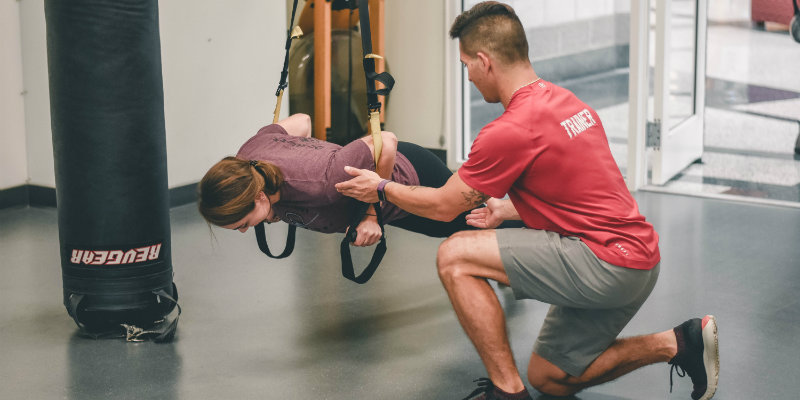 A student doing pushups with a trainer