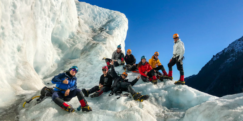 Group of people standing on a glacier in New Zealand