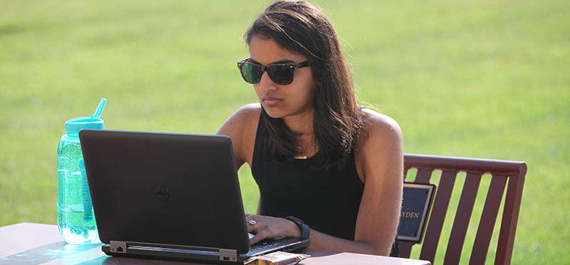Teacher outside at a sunny table with a laptop