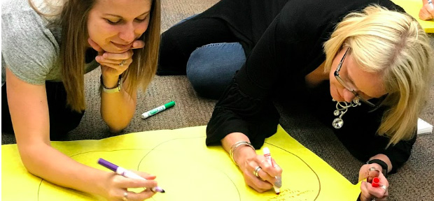 Two teachers working on a poster
