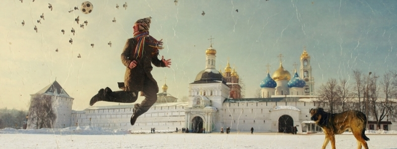 Russian artwork showing a child playing soccer with his dog in the snow, near a city with domed towers.