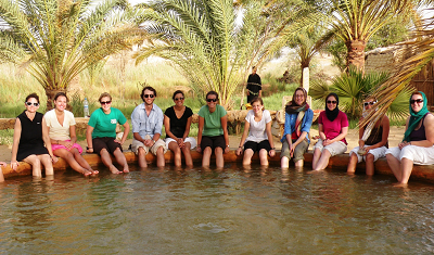 Students sit around an oasis in an Egyptian desert