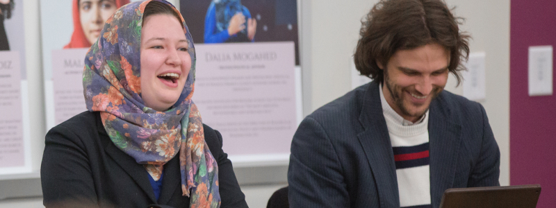 Professor Nathan French shares a laugh with a Muslim student while speaking together on a panel