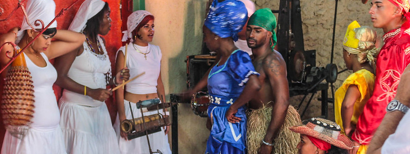Afro-Cuban dances in colorful costumes prepare to perform a rite