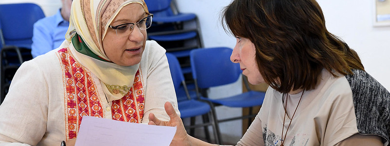 Two women converse over paperwork; one wears hijab