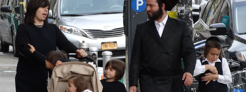 A Hasidic Jewish couple, in traditional dress, walk down a city street with their young children