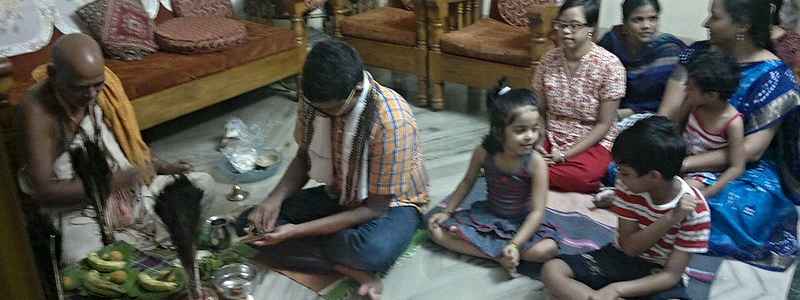 A Hindu family sit on the floor for devotions in front of a home shrine