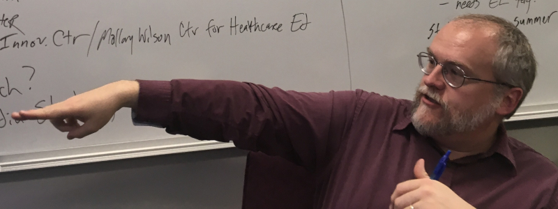 Professor John-Charles Duffy points while sitting in front of a white board