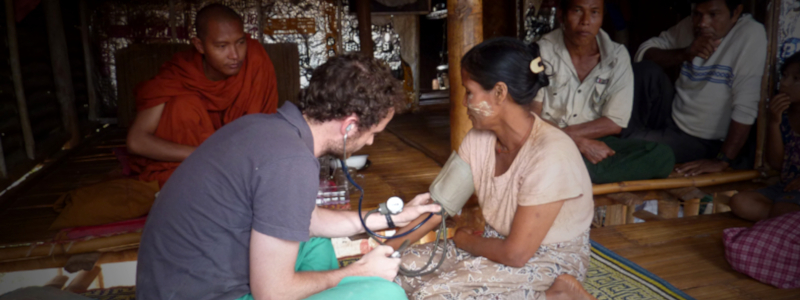 A Buddhist monk observes as a doctor checks the blood pressure of a woman in a rural Burmese community