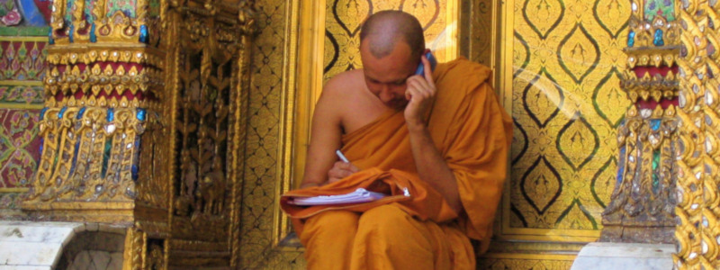 A Buddhist monk sits in front of a temple, talking on a mobile phone while consulting papers held on his lap
