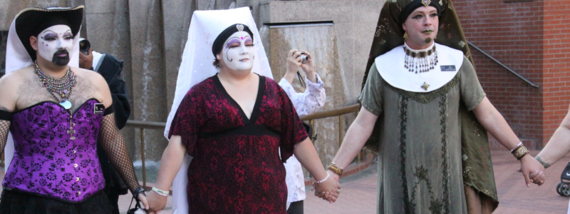 Individuals wearing drag that resembles the habits of Catholic nuns hold hands at a public demonstration