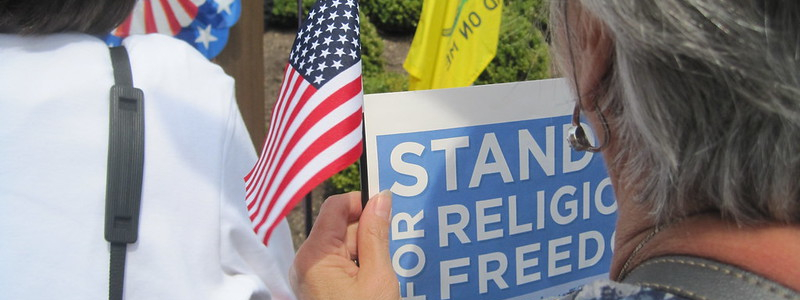 A woman at a political rally holds a miniature US flag and a sign that reads Stand for Religious Freedom