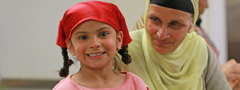 A Sikh child in a modern blouse and a head covering smiles at the camera, while her grandmother, in more traditional dress, observes