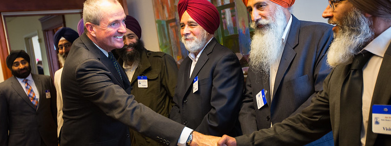 A politician shakes hands with leaders of the local Sikh community