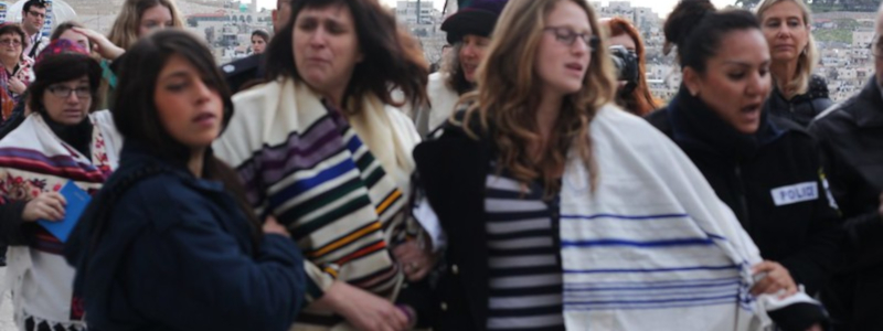 Jewish women wearing prayer shawls are escorted away from a religious protest by police