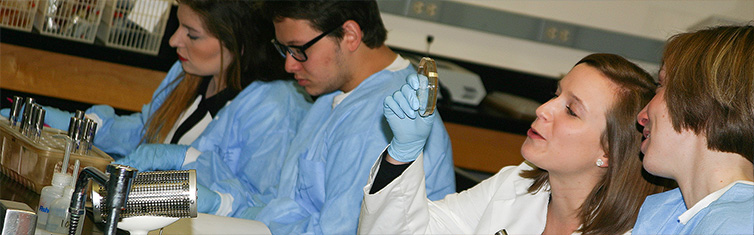 Students wearing protective gear work in lab. One student holds up a specimen