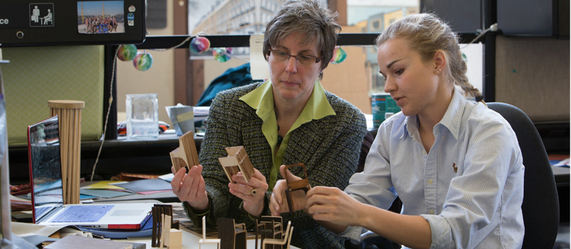 Professor and student converse as they hold and examine small models of furniture