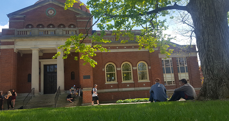 Faculty members sit on the lawn in front of Alumni Hall