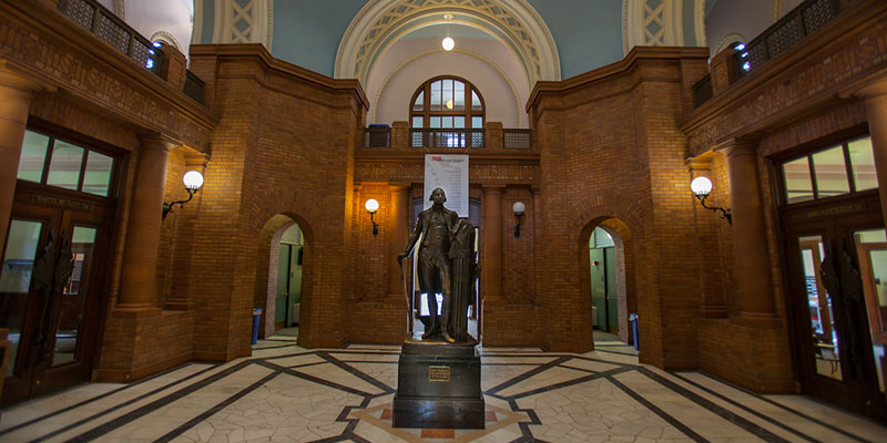Alumni Hall interior showing rotunda walls, statue, and flooring
