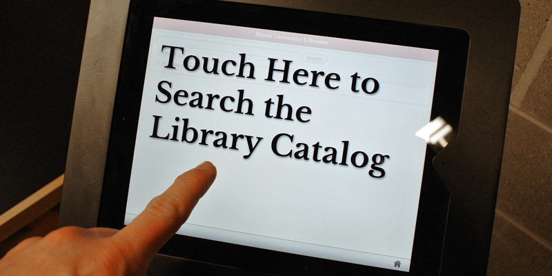 A library touchscreen with a pointing finger. Text: Touch here to search the library catalog