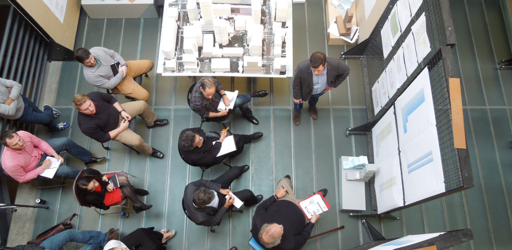 An overhead view of a student presenting to faculty