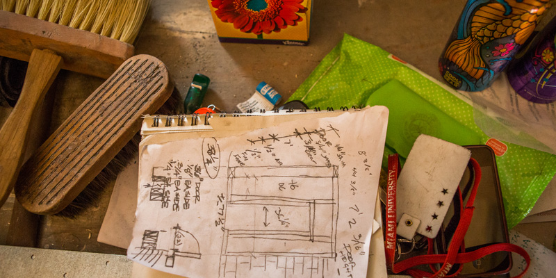 Construction plans are laid out on a table. Other items include a Miami lanyard and assorted construction tools