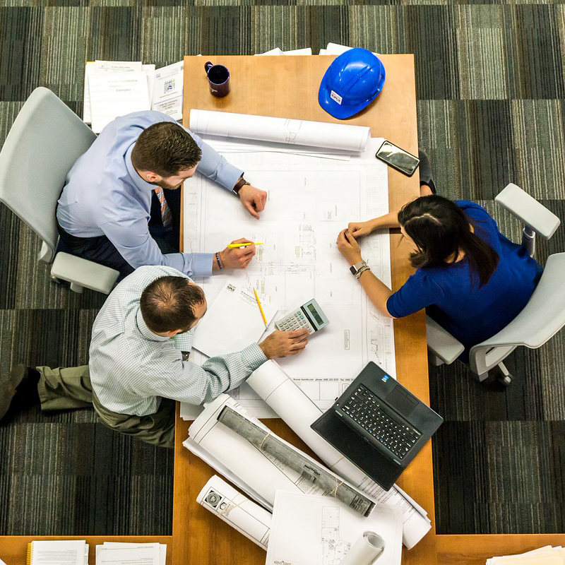 Aerial view of a group of architects at a table examining blueprints